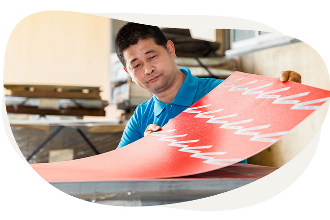 Man checking a newly printed tin plate